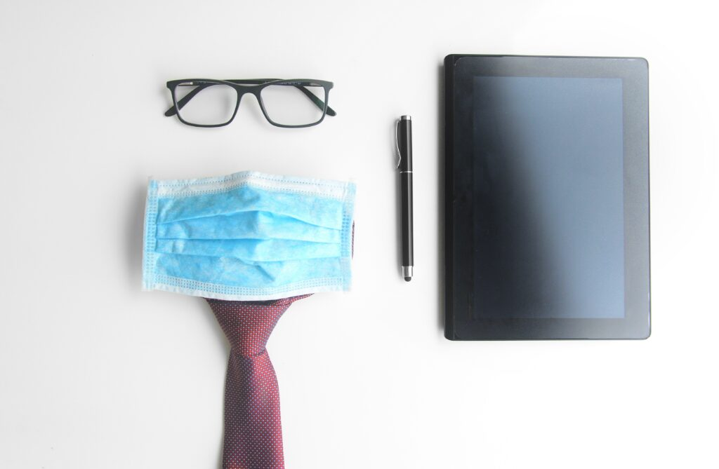 Business Man Work Kit During Pandemic. Tablet, Electronic Pen, Glasses, Tie And Face Mask On A White Background. Business Man Protection Against Covid 19.