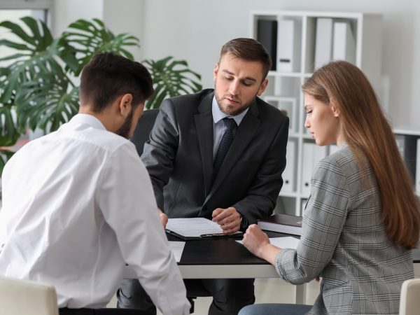 Unhappy Young Couple Visiting Divorce Lawyer In Office